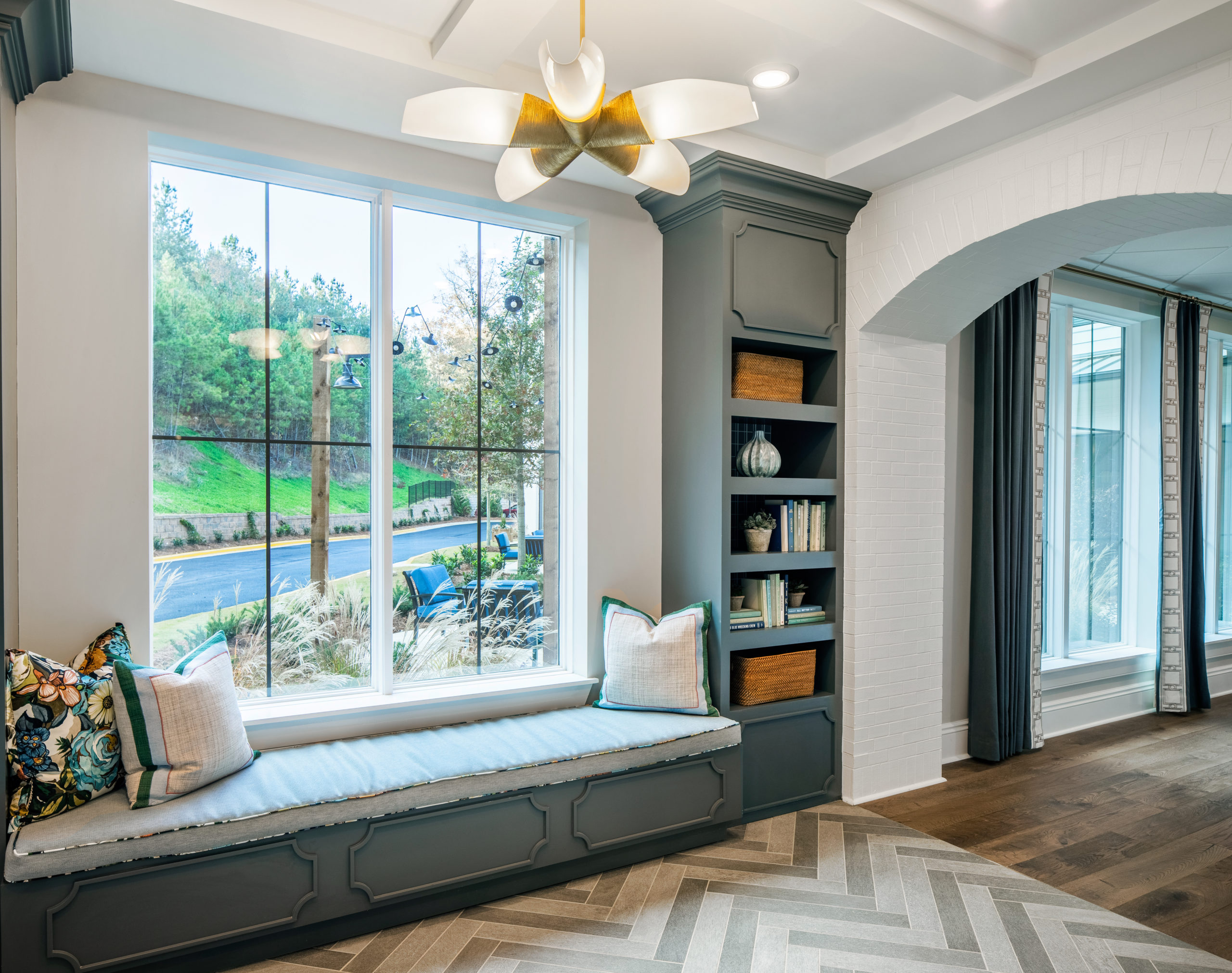 Longleaf common space window with bench setting and pillows, gray paneling and bookshelf, view of patio and green trees