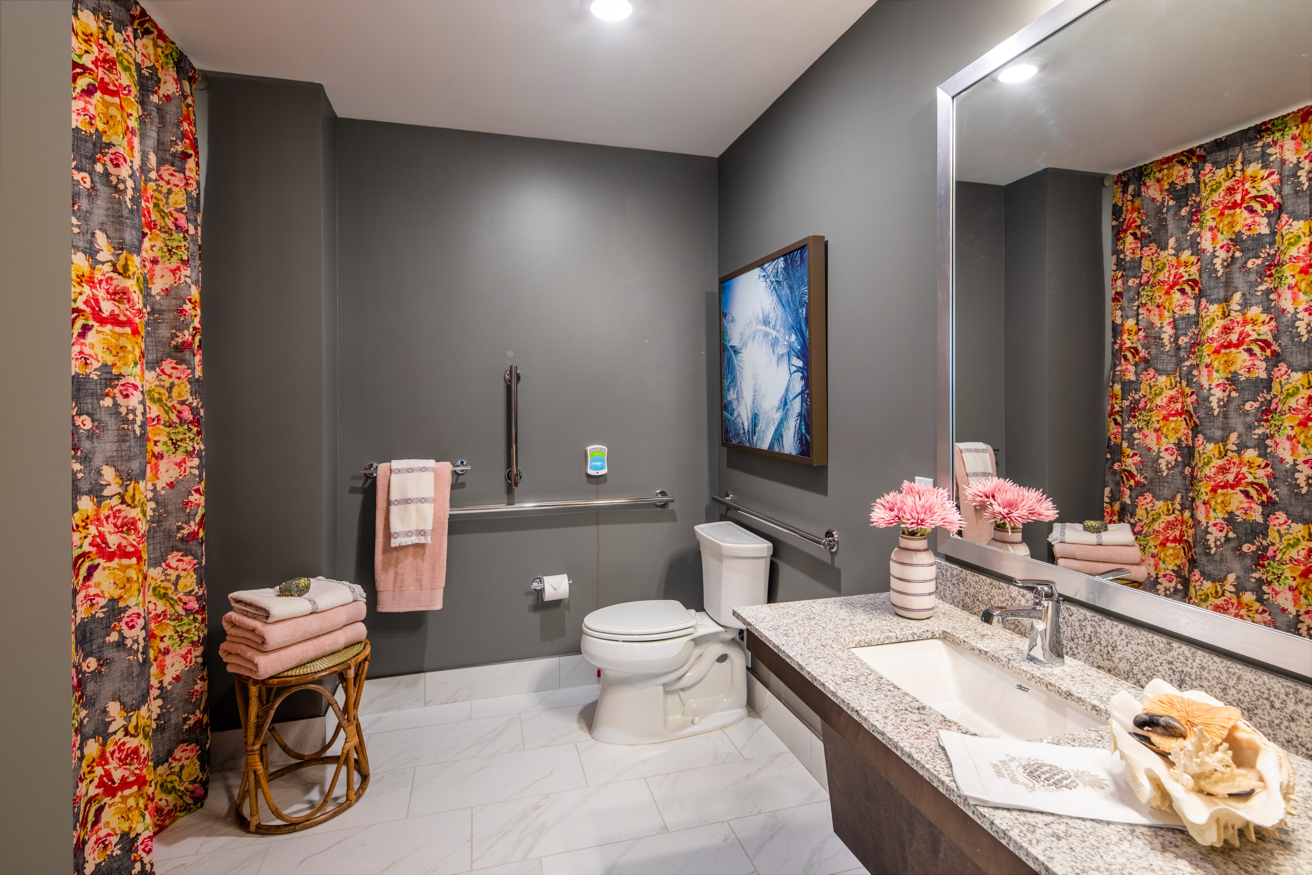 Bathroom vanity, toilet and shower with floral curtains, grey walls white floor in Longleaf assisted living model apartment