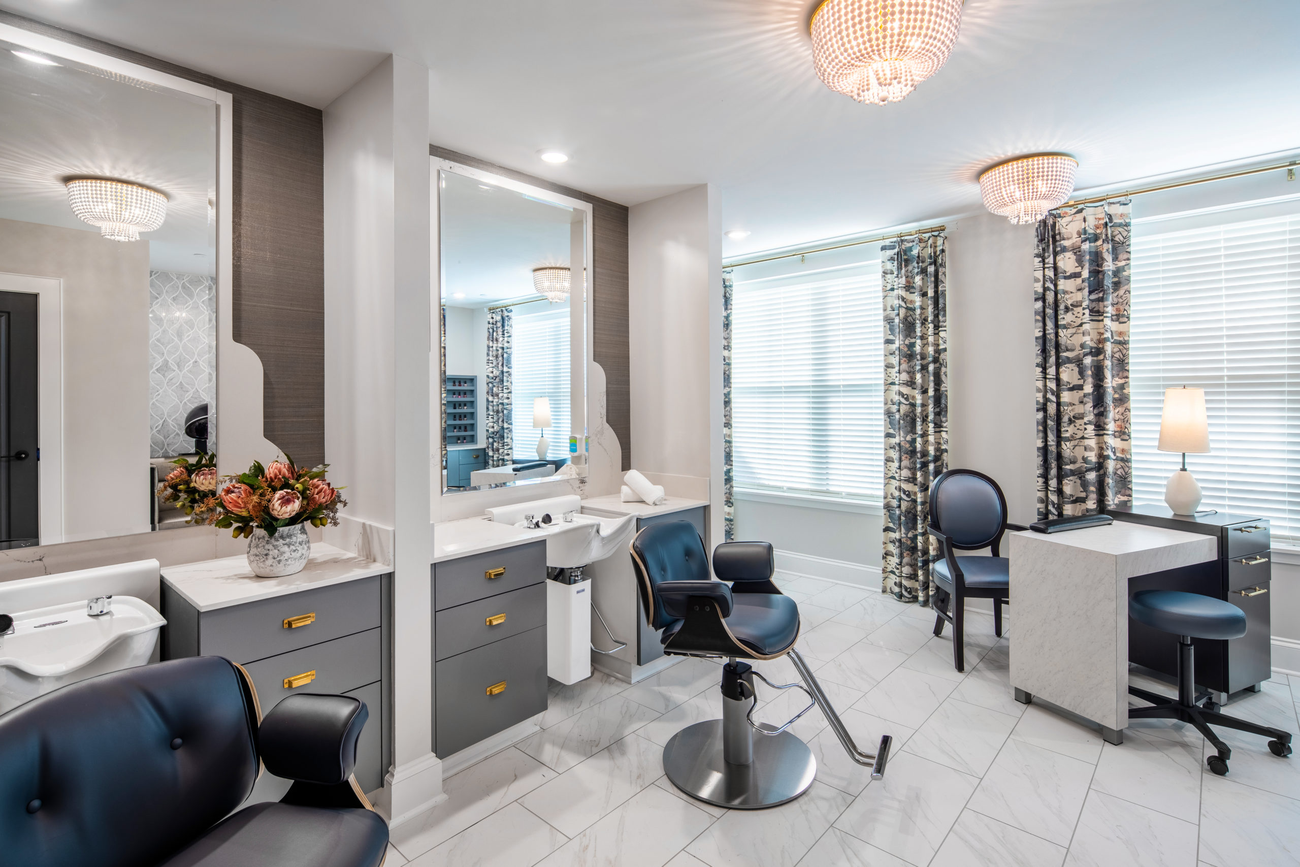 Two stylist stations with client chairs, white sinks and countertops, gray cabinets and mirrors with manicure table and chairs to right by windows in Longleaf salon