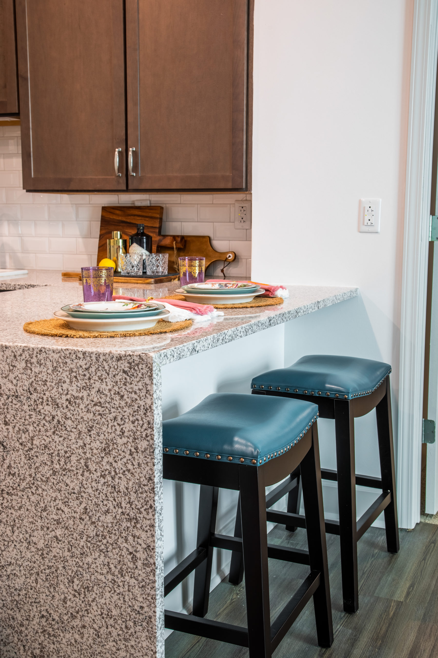 Two teal and brown stools at breakfast bar with waterfall granite countertops in kitchen with white wall, white backsplash and brown cabinets in Longleaf assisted living model apartment