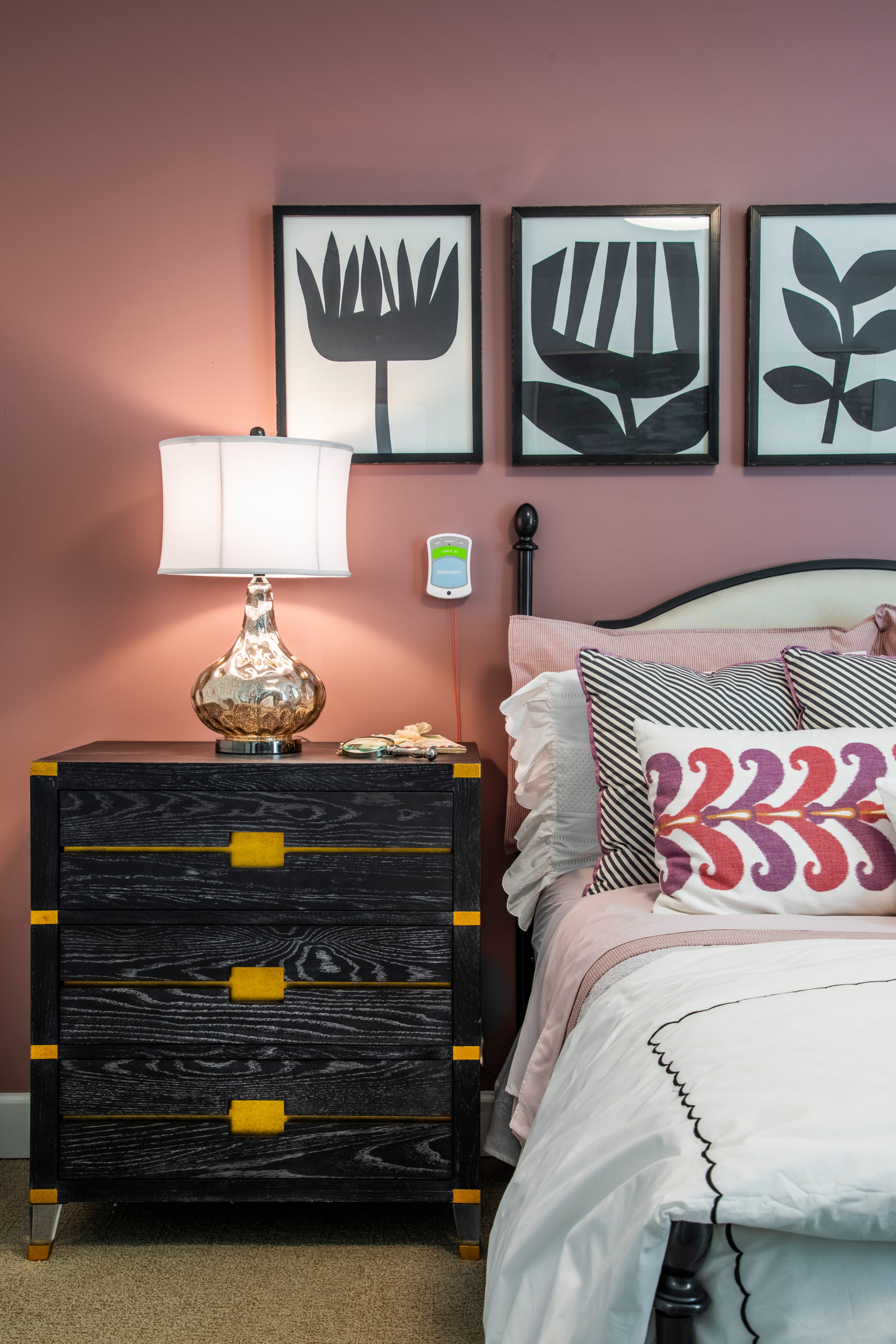 Left side view of white bed and colorful pillows with black and gold nightstand and glass lamp with white shade and black and white wall art on mauve wall in Longleaf assisted living model apartment