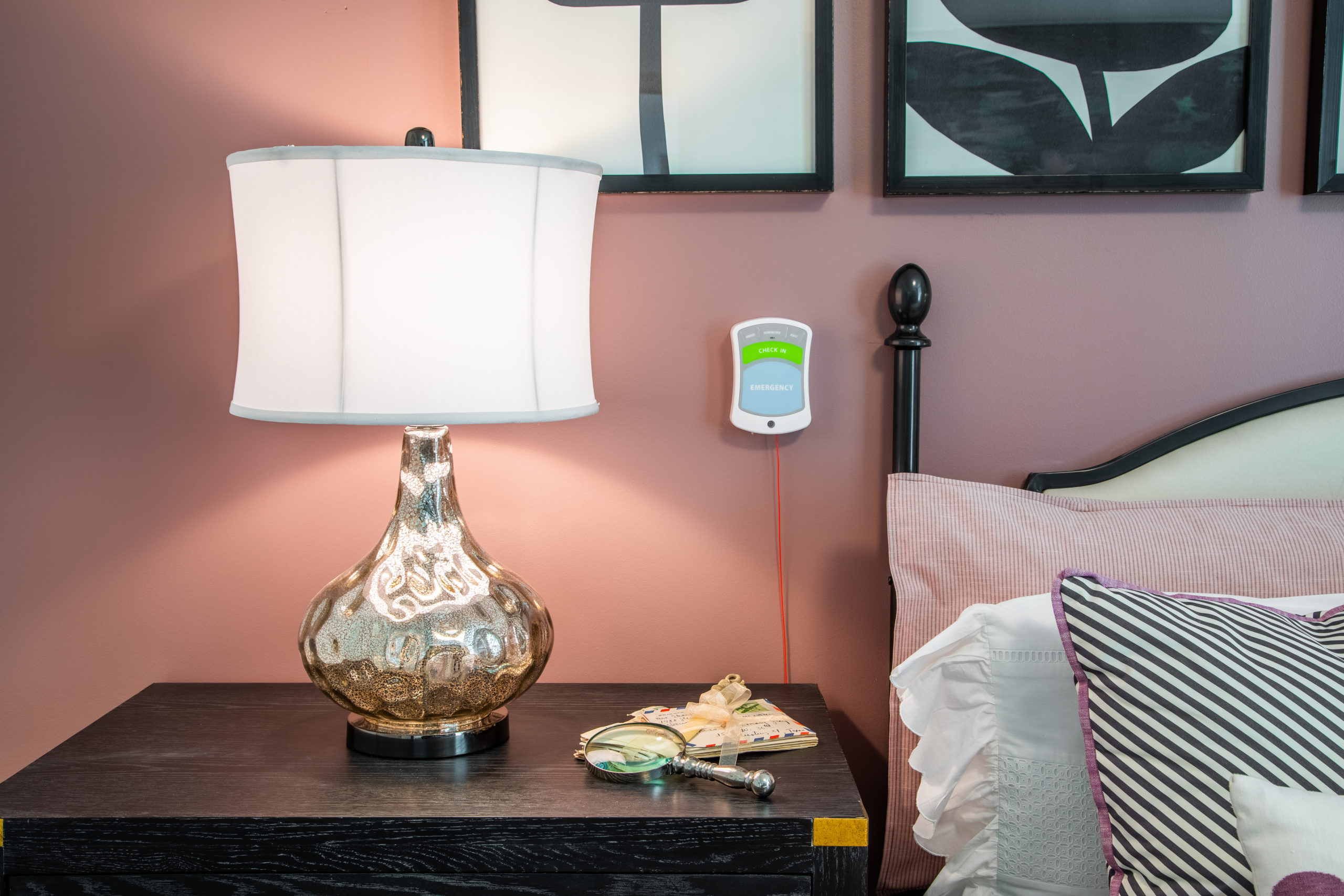 White and glass lamp, magnifying glass and letters sitting on black nightstand next to bed in Longleaf assisted living model apartment