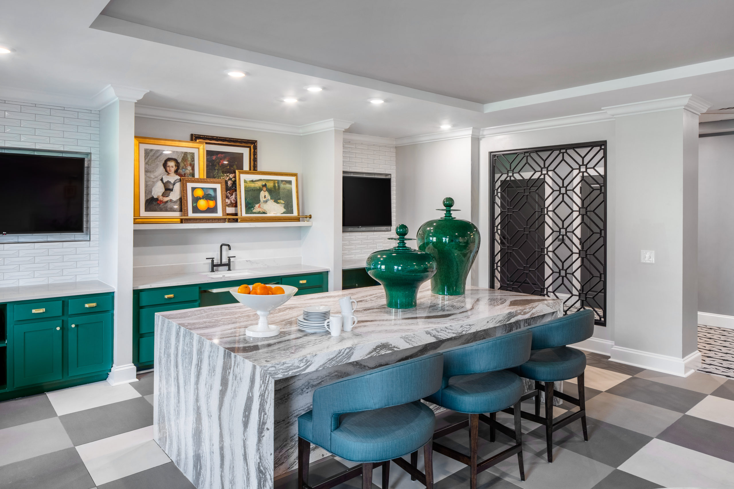 Breakfast bar with three blue chairs, checkered floor and green cabinets and white walls with framed art and TVs at back of Longleaf Bistro