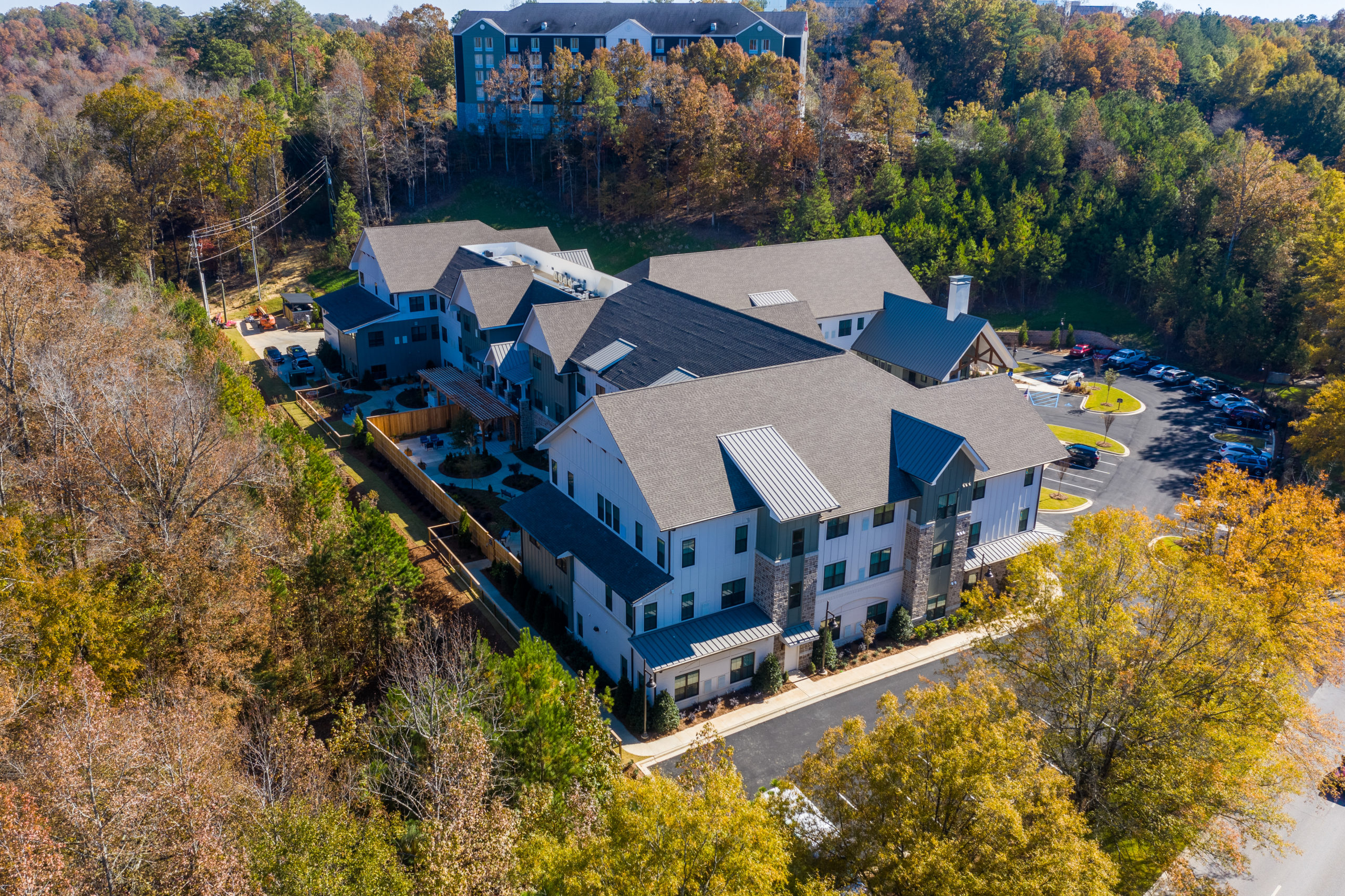 Aerial view of Longleaf community looking at left side of community with fenced memory care patios in view and front entrance to the right and fall trees surrounding community