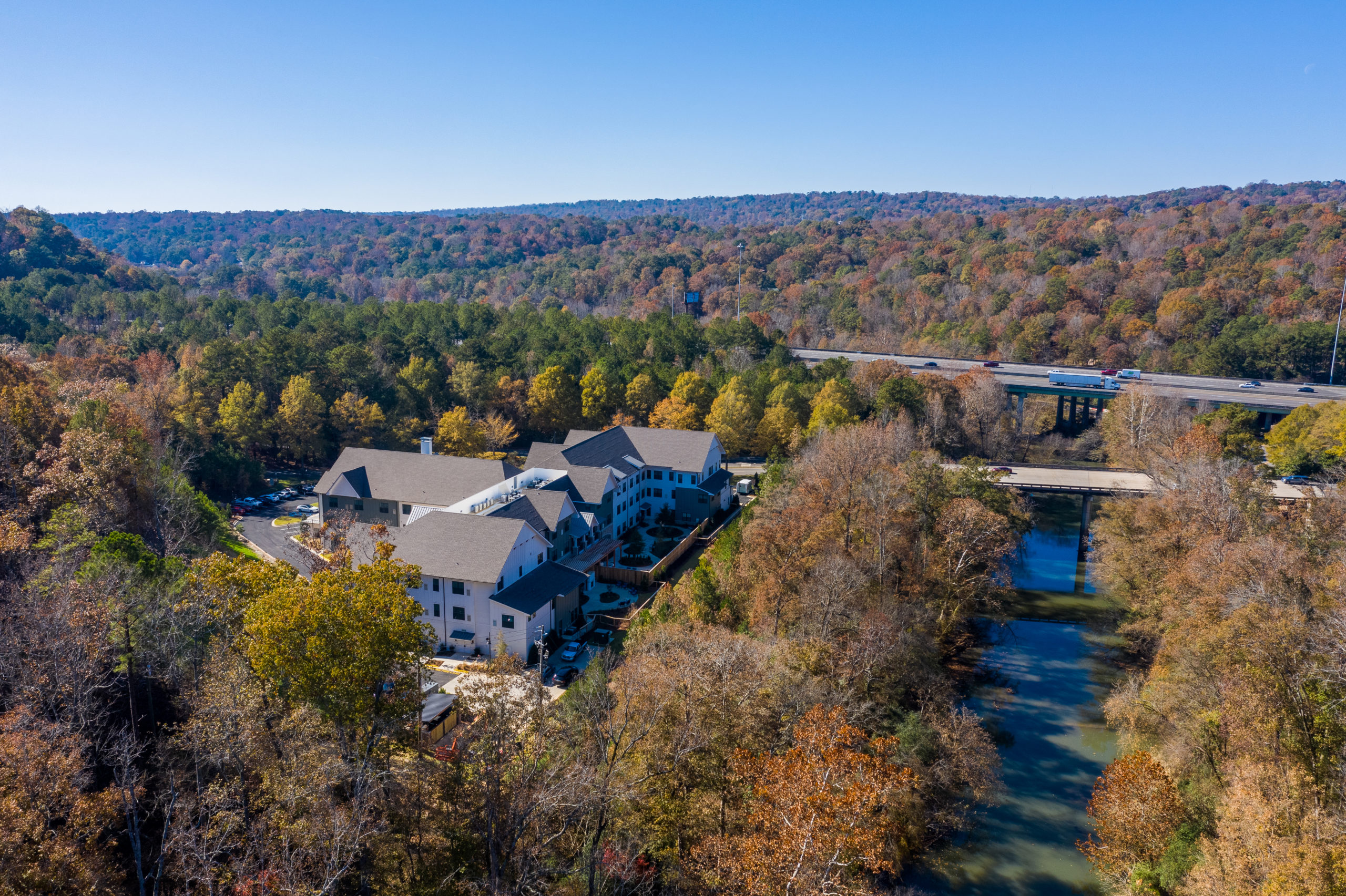 Aerial view of Longleaf community with river view to the right and community to the left surrounded by trees with fall colors