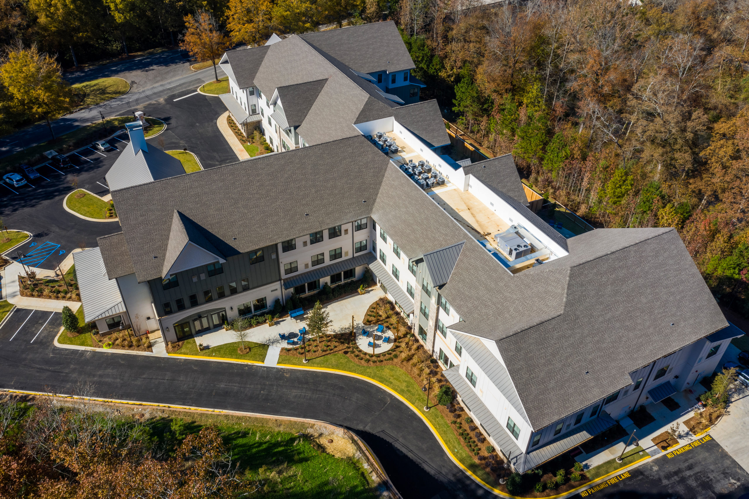 Aerial view of back of Longleaf community with blue patio furniture in view and treed area to right
