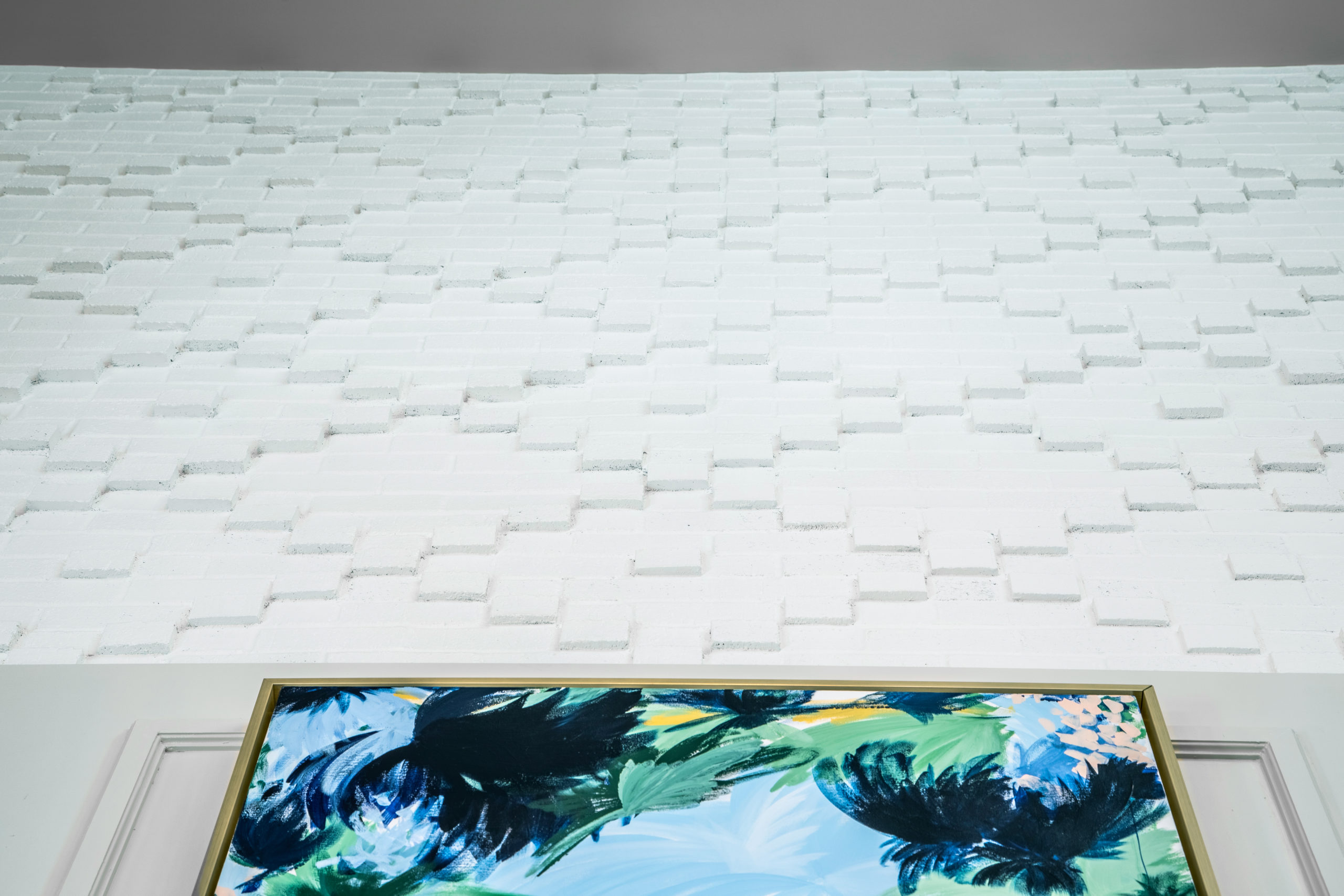 Close up view looking up at white textured wall with partial view of blue, green and yellow framed art in Longleaf foyer