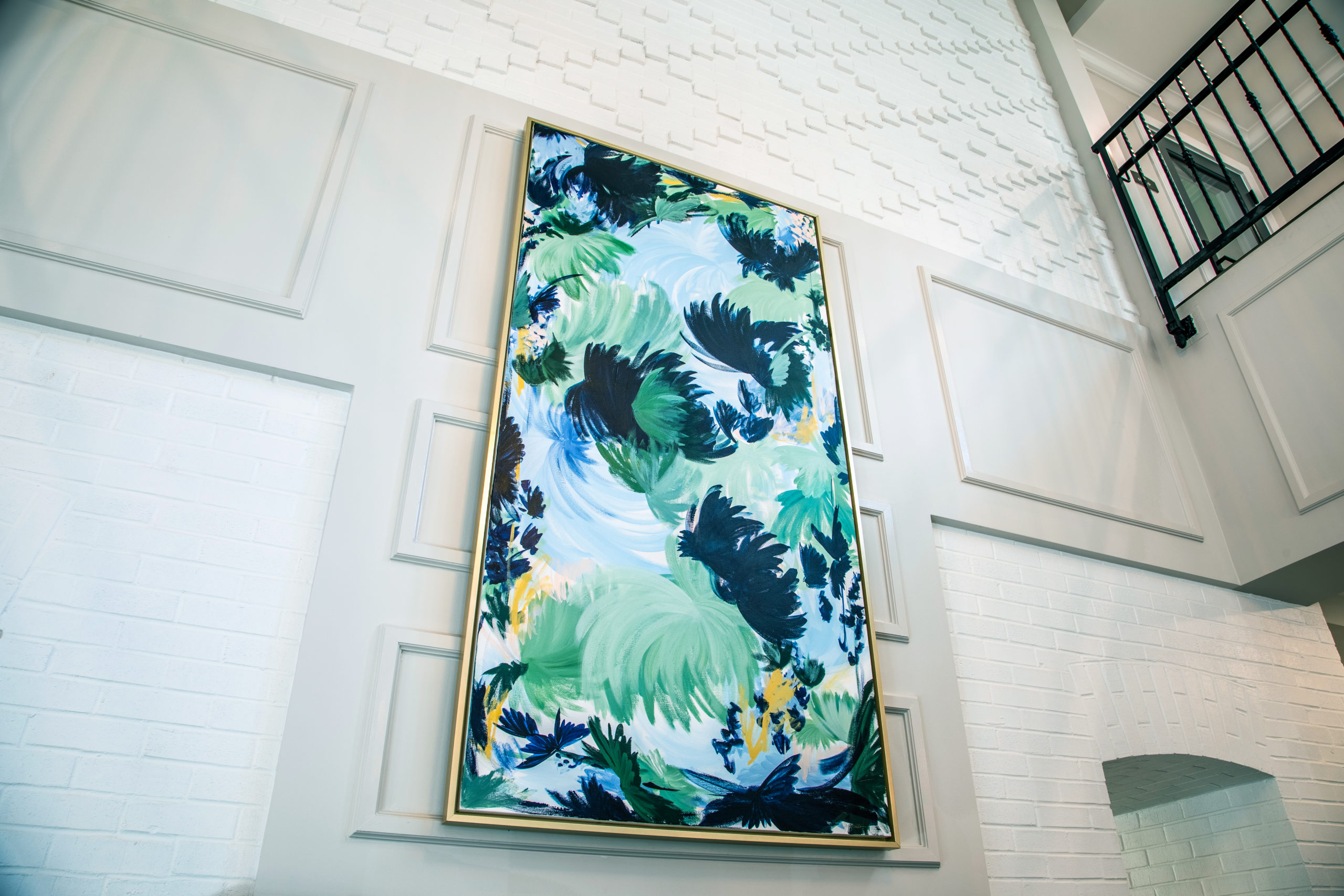 Blue, green and yellow framed art on white wall in Longleaf foyer