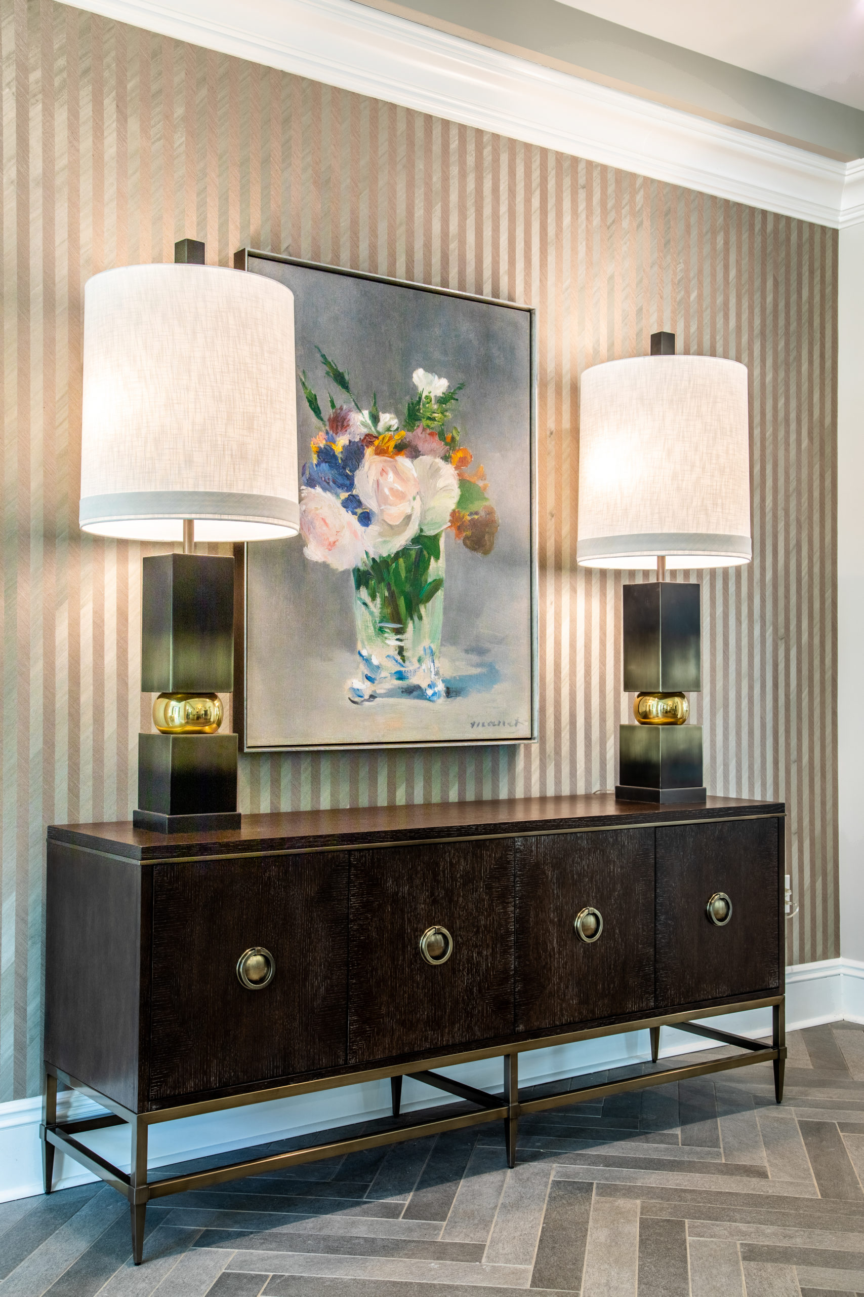 Brown table under framed floral art centered by two lamps with white shades in Longleaf common space