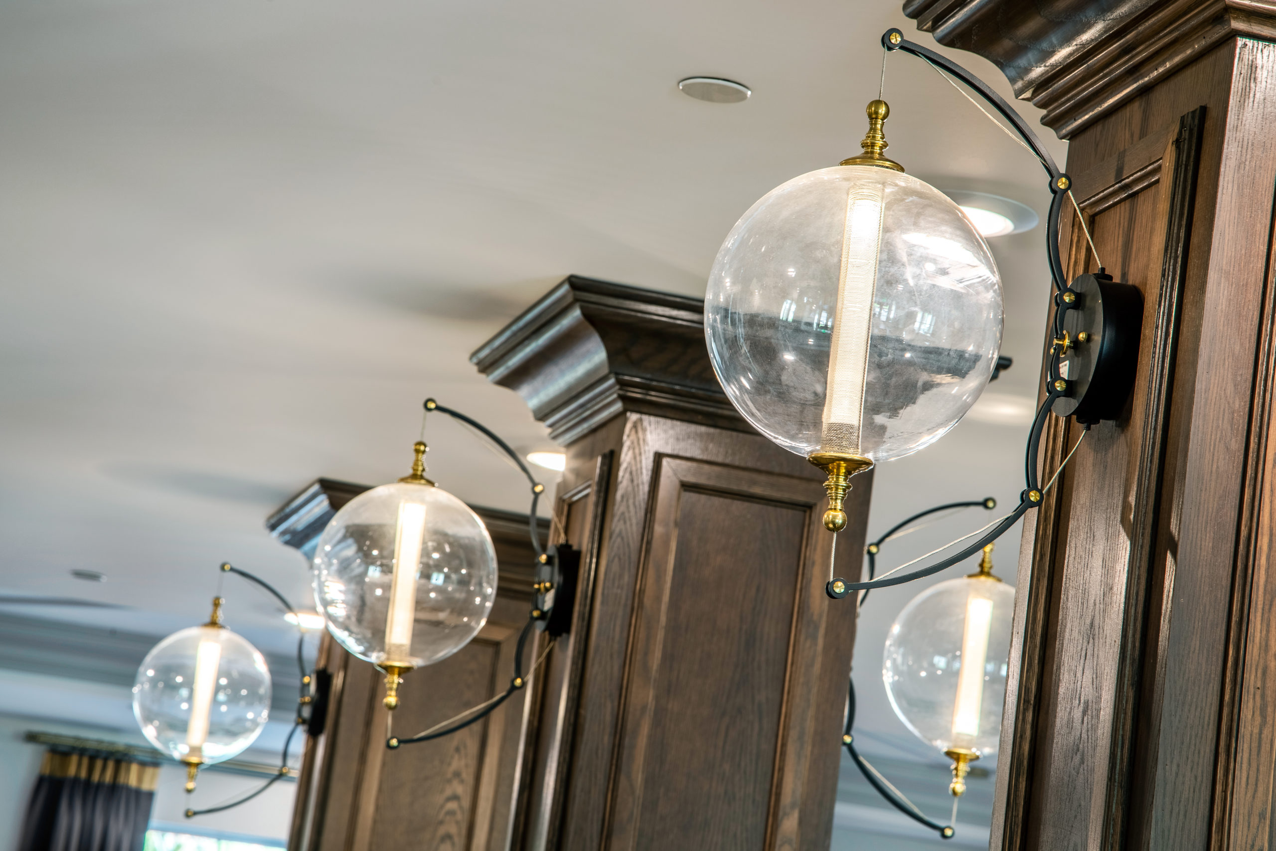 Glass globe light fixtures with gold and black mounting on wooden columns in Longleaf common space