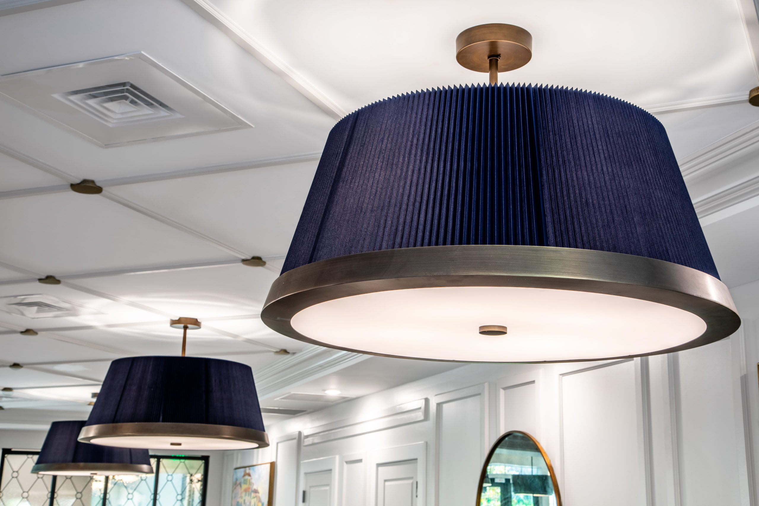 Blue lamp shades on light fixtures with bronze fixtures on white ceiling in Longleaf common space