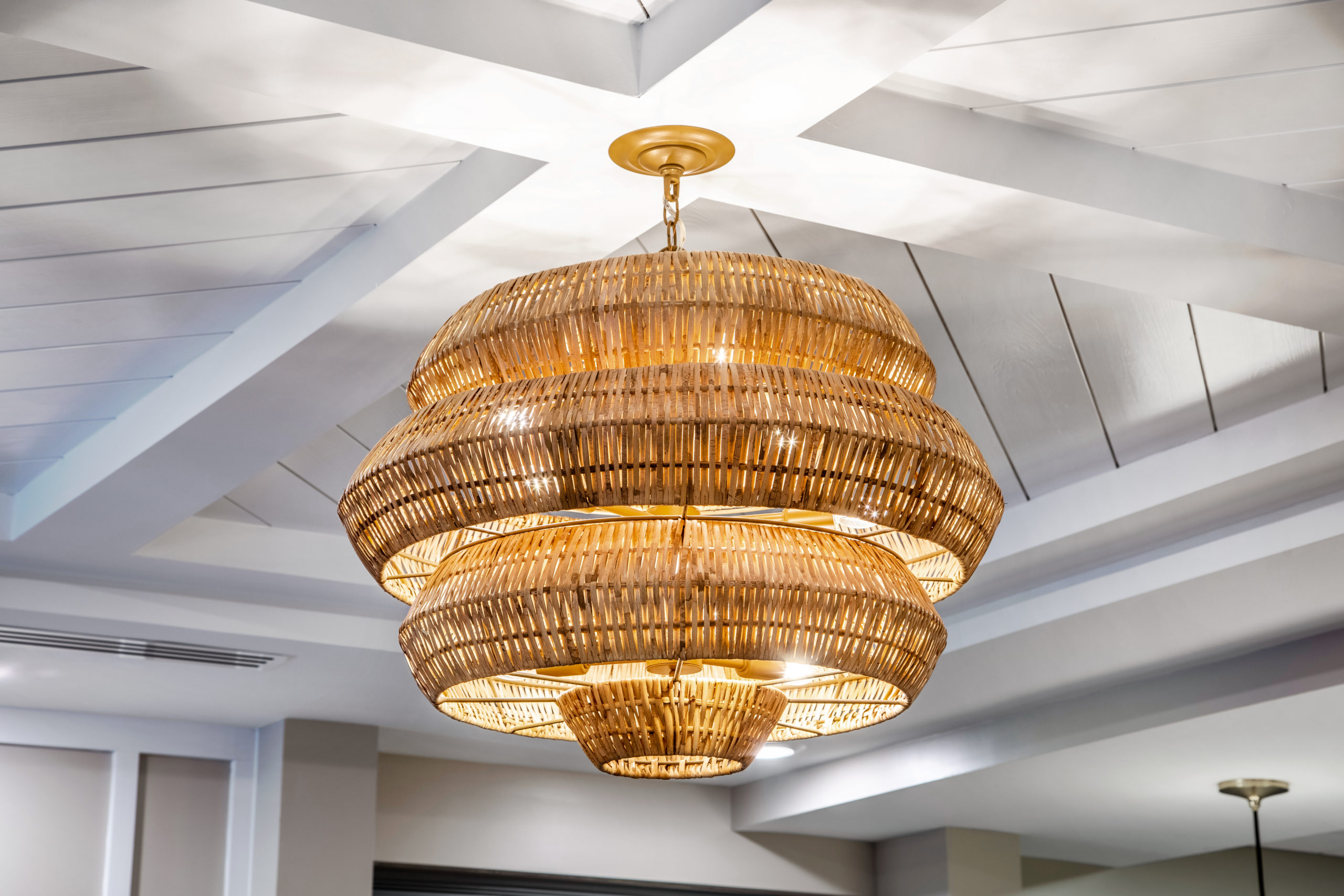 Basket weave like light fixture hanging from white wooden ceiling in Longleaf common space