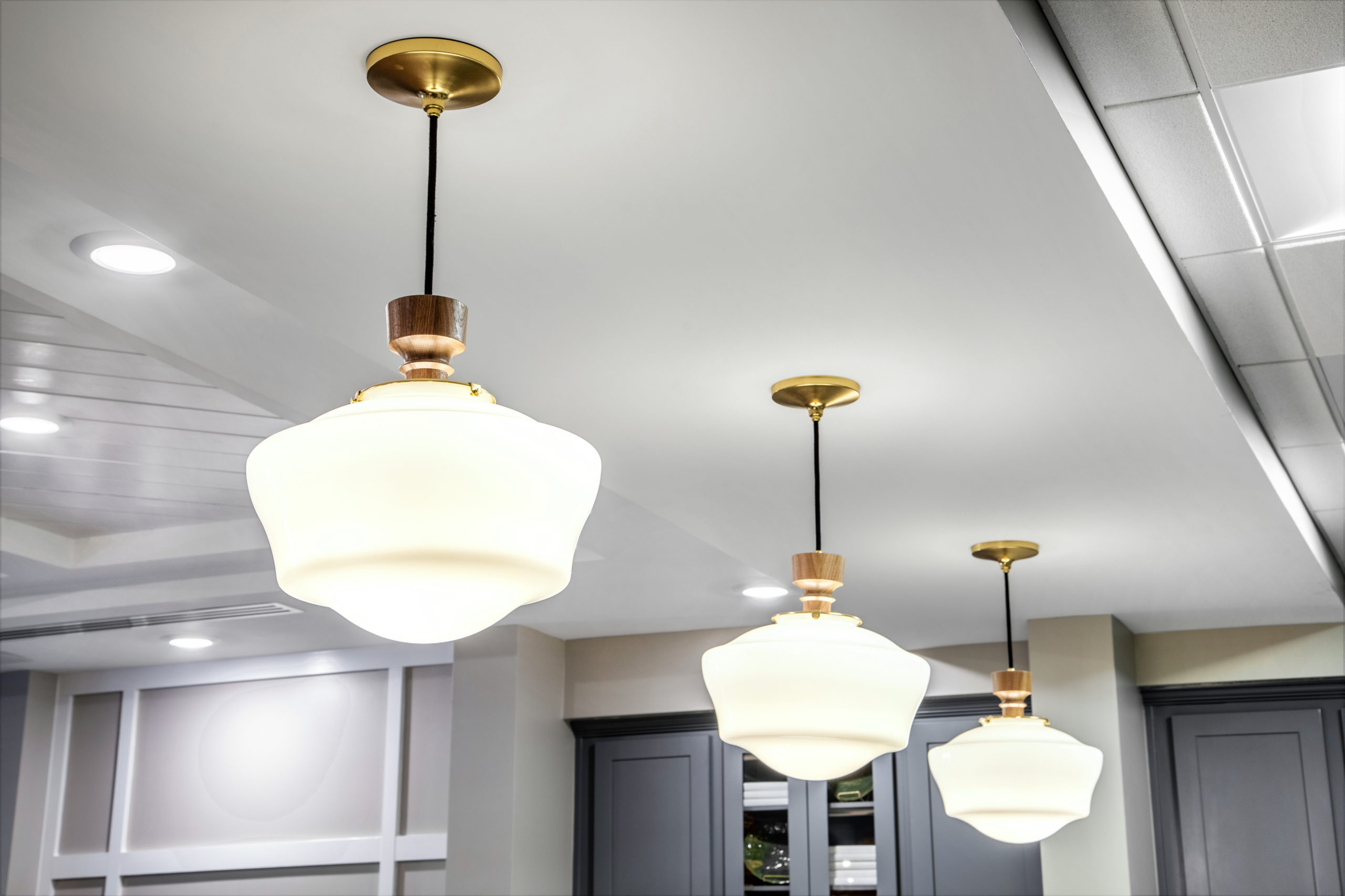 White and gold light fixtures hanging from white ceiling in Longleaf common space