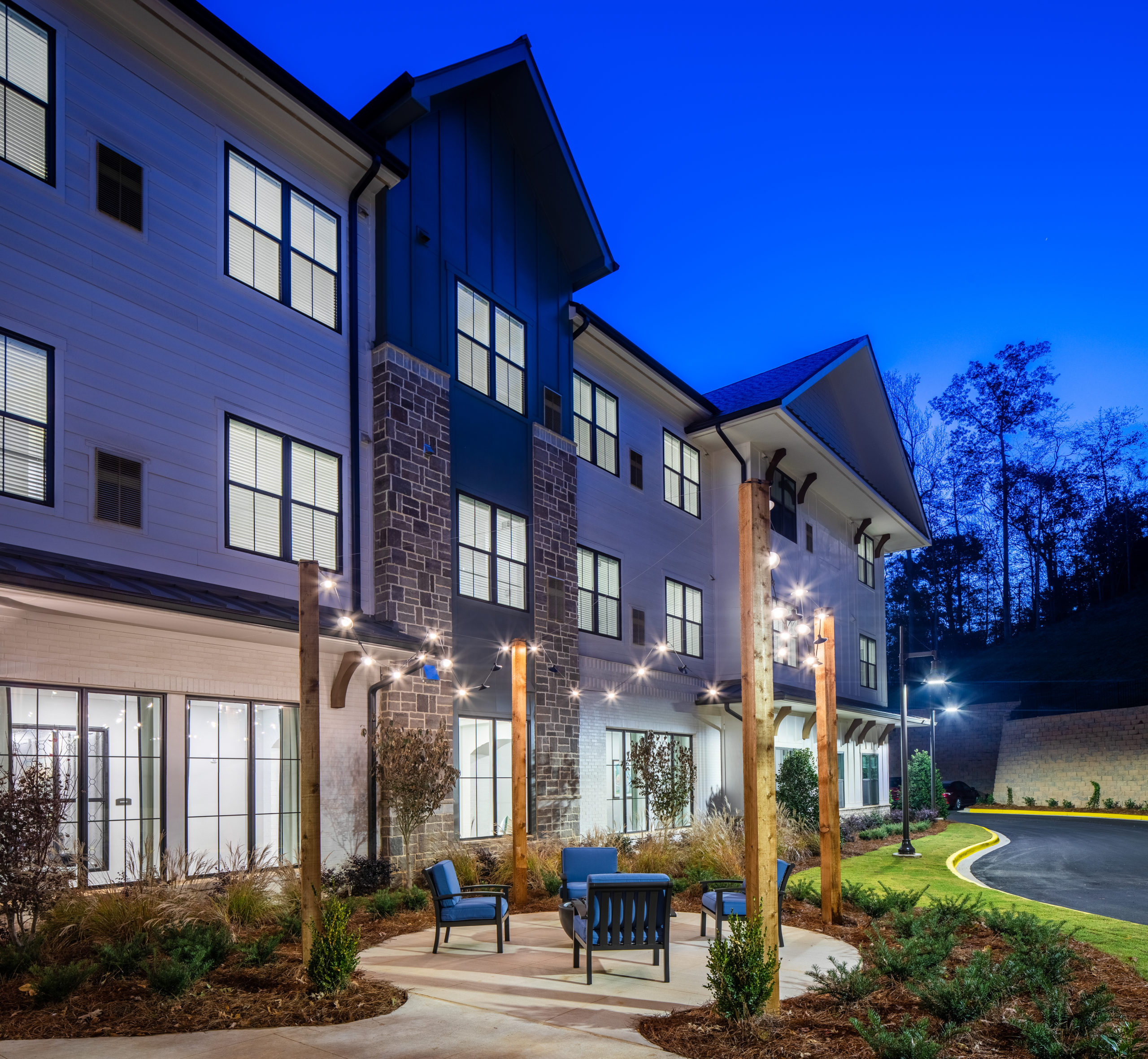 Rear exterior view of Longleaf Liberty Park at night with lights on and vivid blue skies