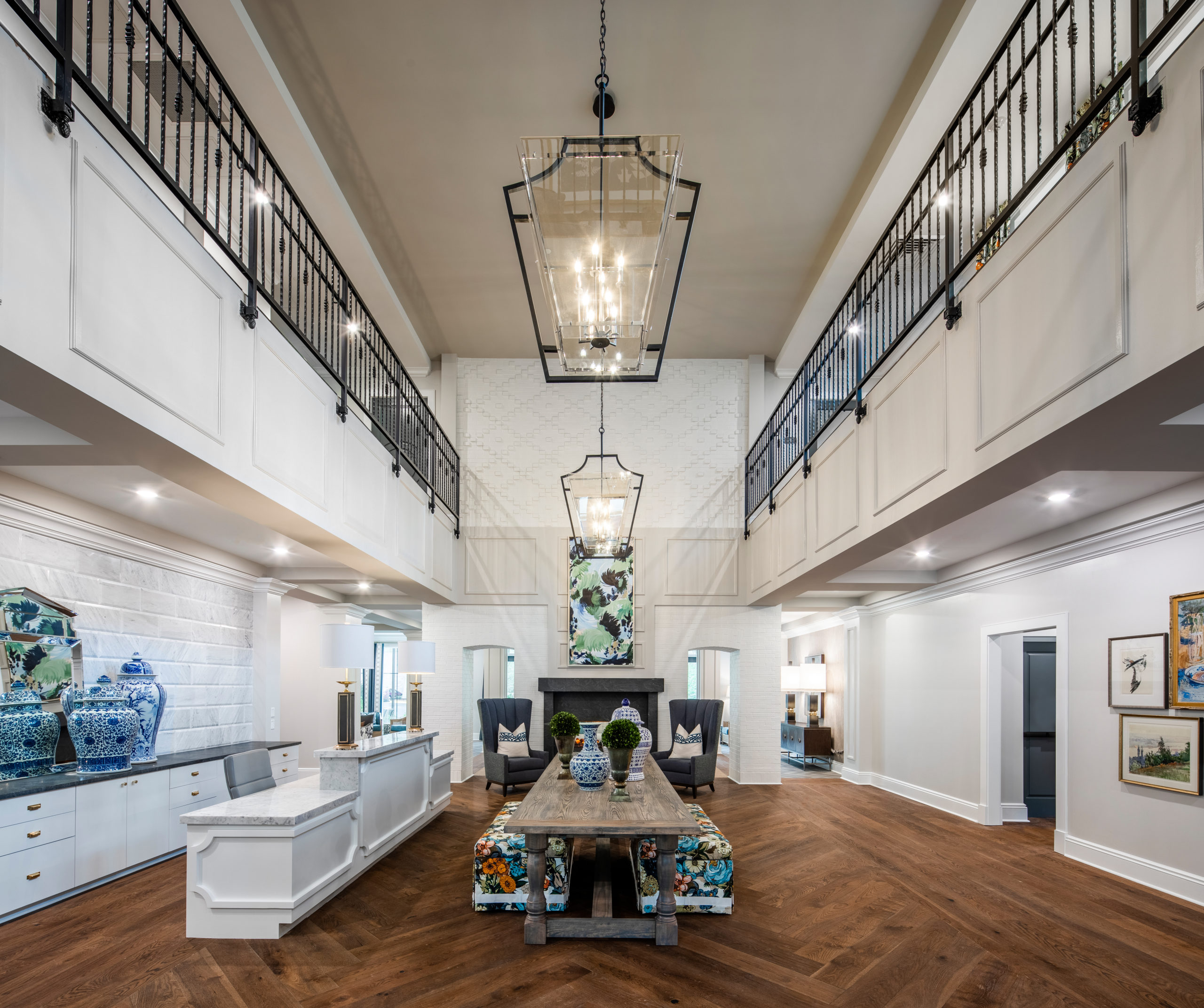 Longleaf foyer with white front desk at left, long wood table in center holding blue/white vases, greenery in pots and floral benches underneath, and open to second floor above with black metal railing, glass light fixtures, see-through fireplace at back of room with chairs