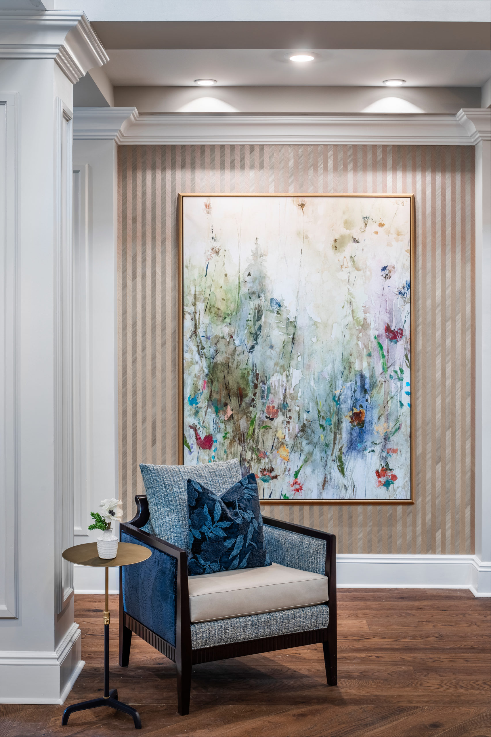 Longleaf common space with blue and tan chair, gold table, flowers in white vase, floral painting on wall behind