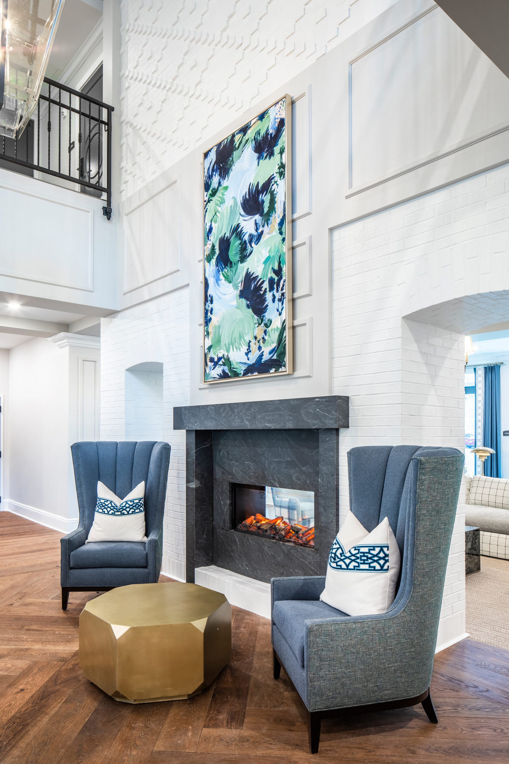 Longleaf foyer with gray see-through fireplace, blue chairs, gold table and blue/green painting on white wall