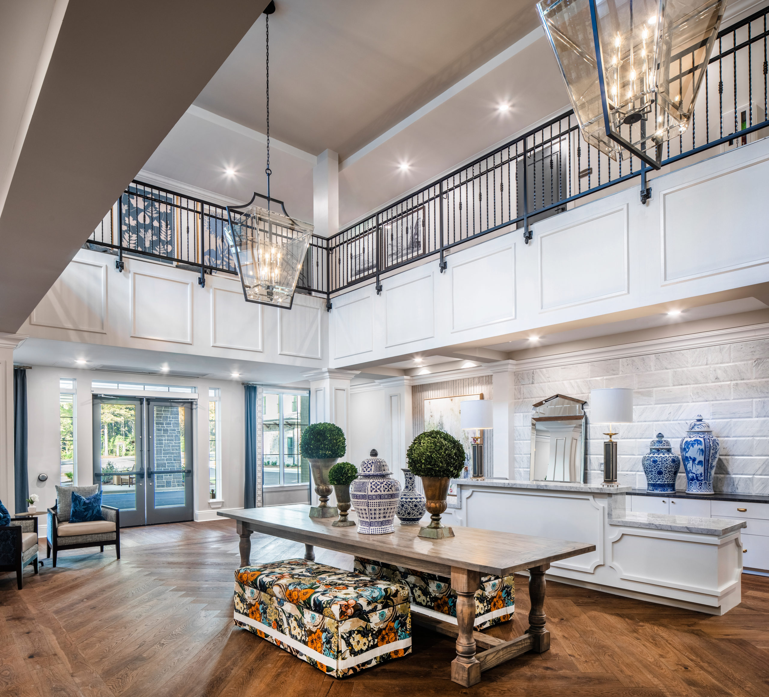 Longleaf foyer looking at entrance to left, white desk at right and long wood table in center holding blue/white vases, greenery in pots and floral benches underneath, and open to second floor above with black metal railing, glass light fixtures