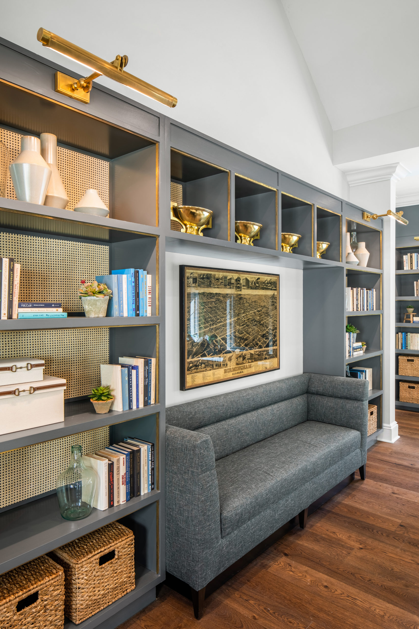 Longleaf library with gray shelves filled with books, gold and white decor, wicker baskets and gray sofa