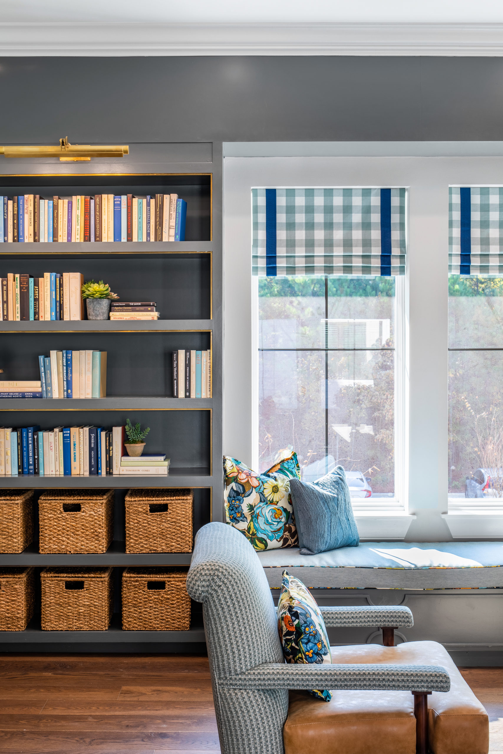 Longleaf library with window above bench seating, blue pattern and brown leather chair, gray wood bookcases with books and baskets on shelves