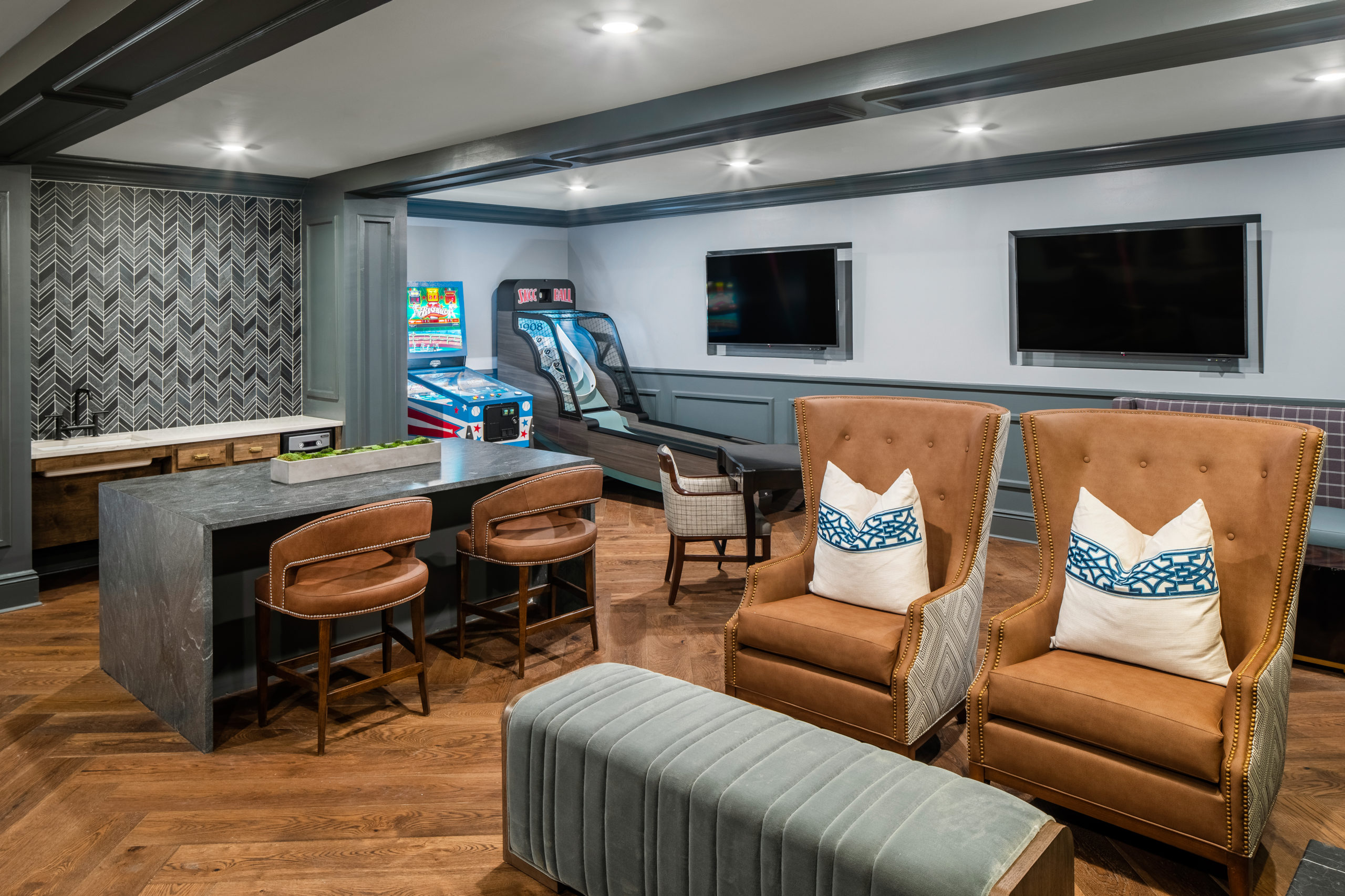 Longleaf lounge bard and stools at left, arcade games to right of bar, two brown leather chairs with white and blue pillows at right with light green ottoman