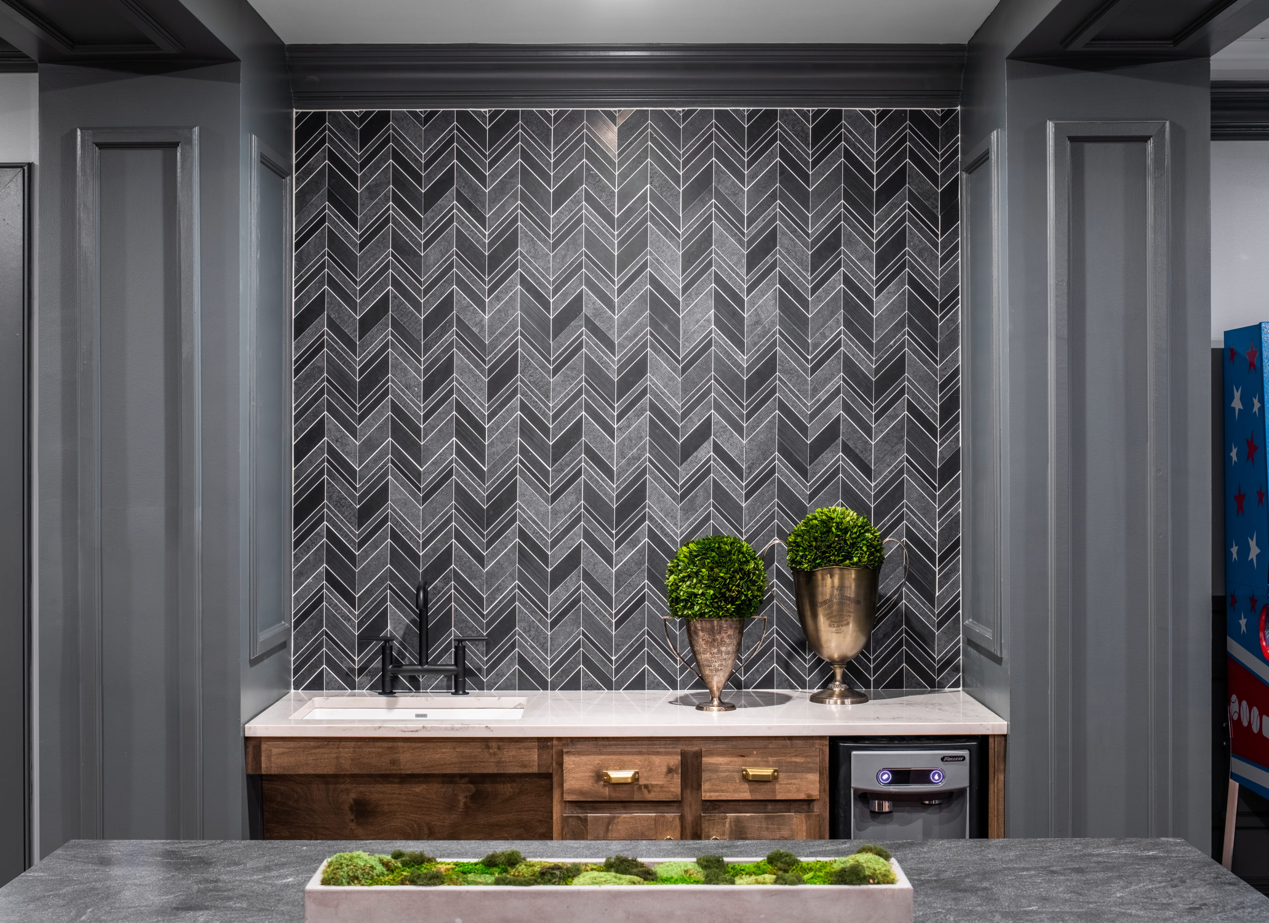 Longleaf lounge top of bar with gray chevron backsplash and gray walls, brown cabinets with white countertop and sink greenery in pots and vases