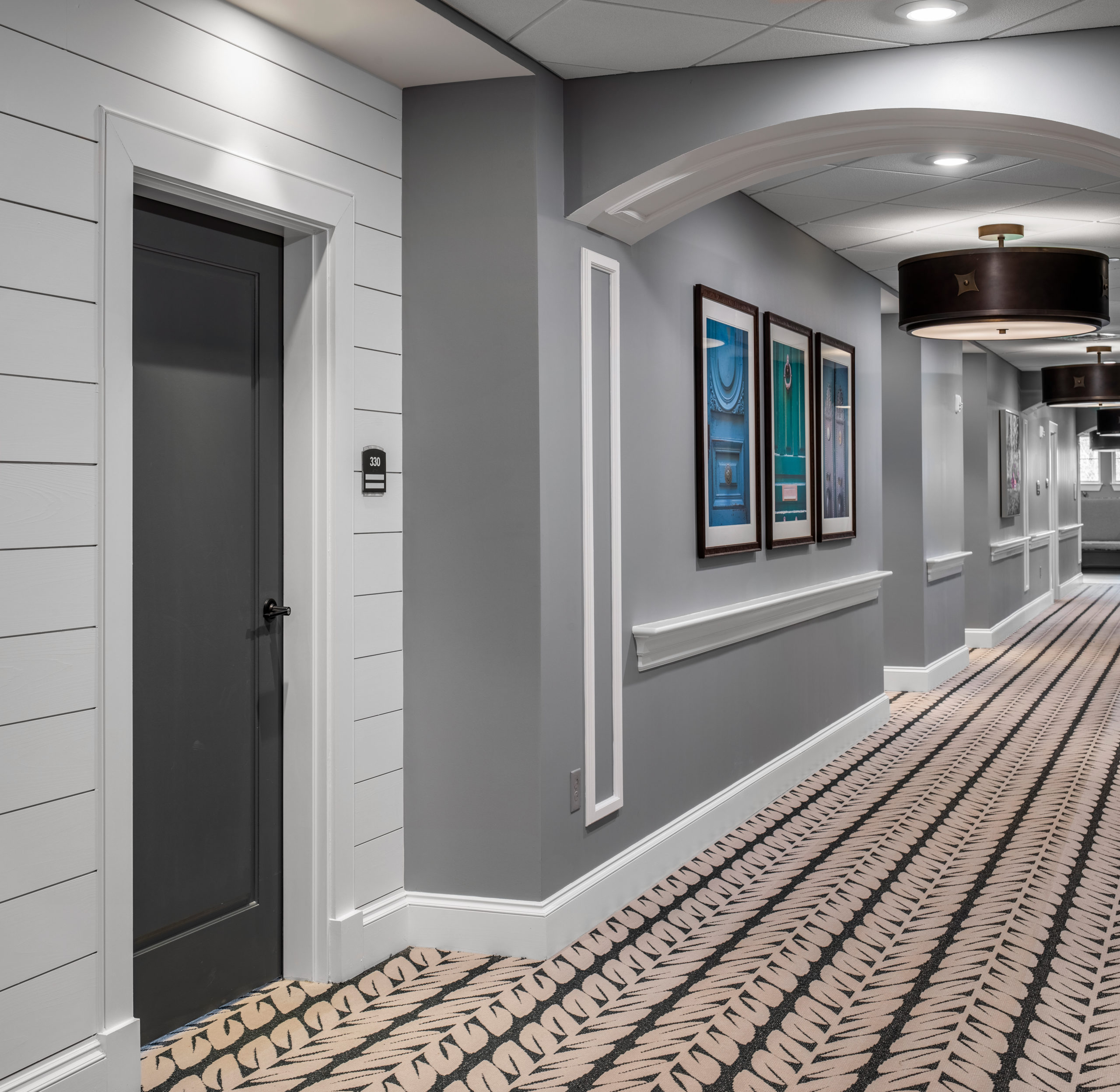 Longleaf hallway with white walls and residents' blue doors at left, gray walls to right of door