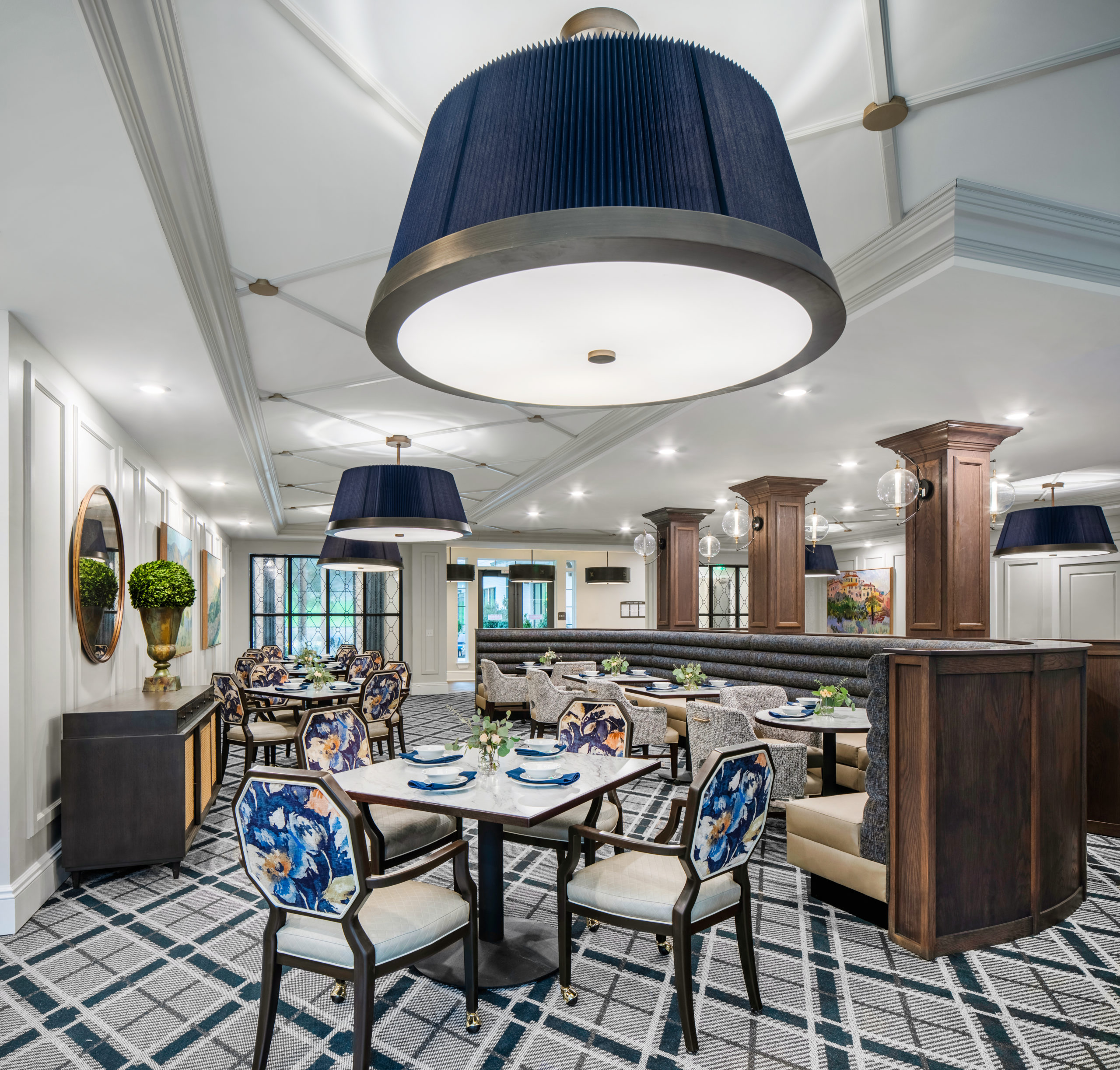 Longleaf main dining room with blue light fixtures, blue and beige curved booth, tables and floral backed chairs with wood columns and globe light fixtures at right, buffet table, mirror and potted plant at left