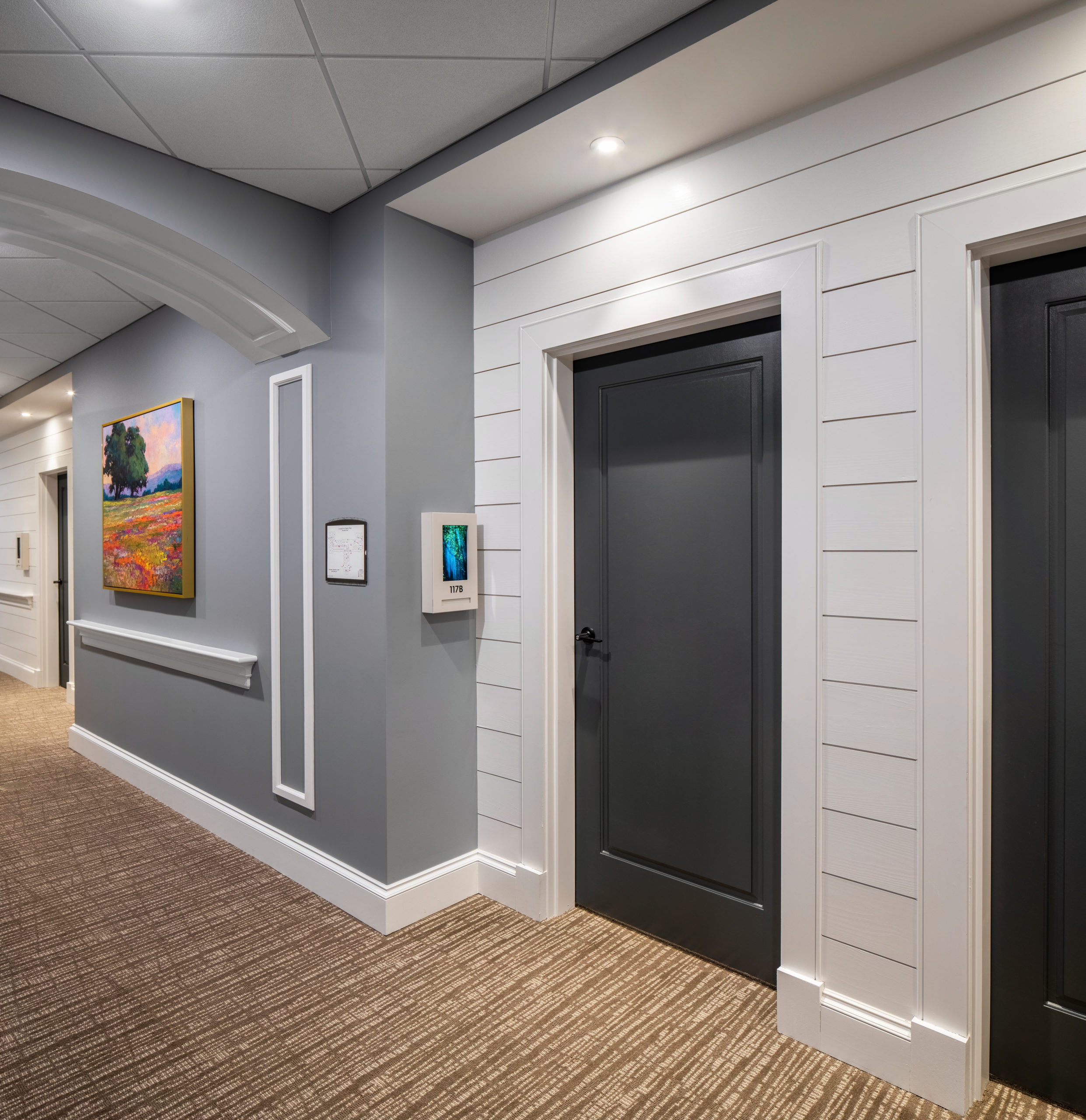 Longleaf hallway with white walls and residents' blue doors at right, gray walls at left