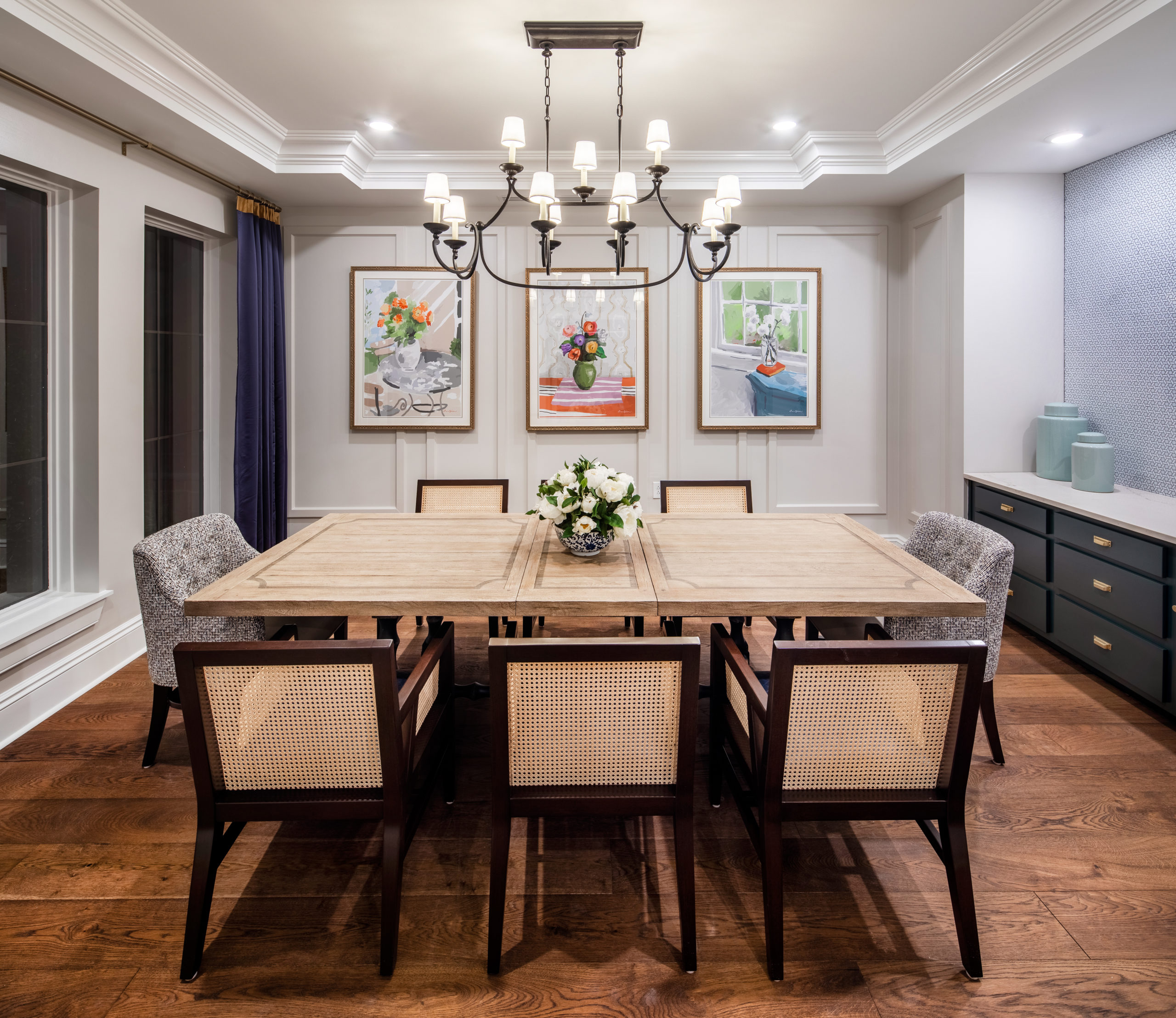 Longleaf private dining room with formal table and chairs with framed art on walls and chandelier above
