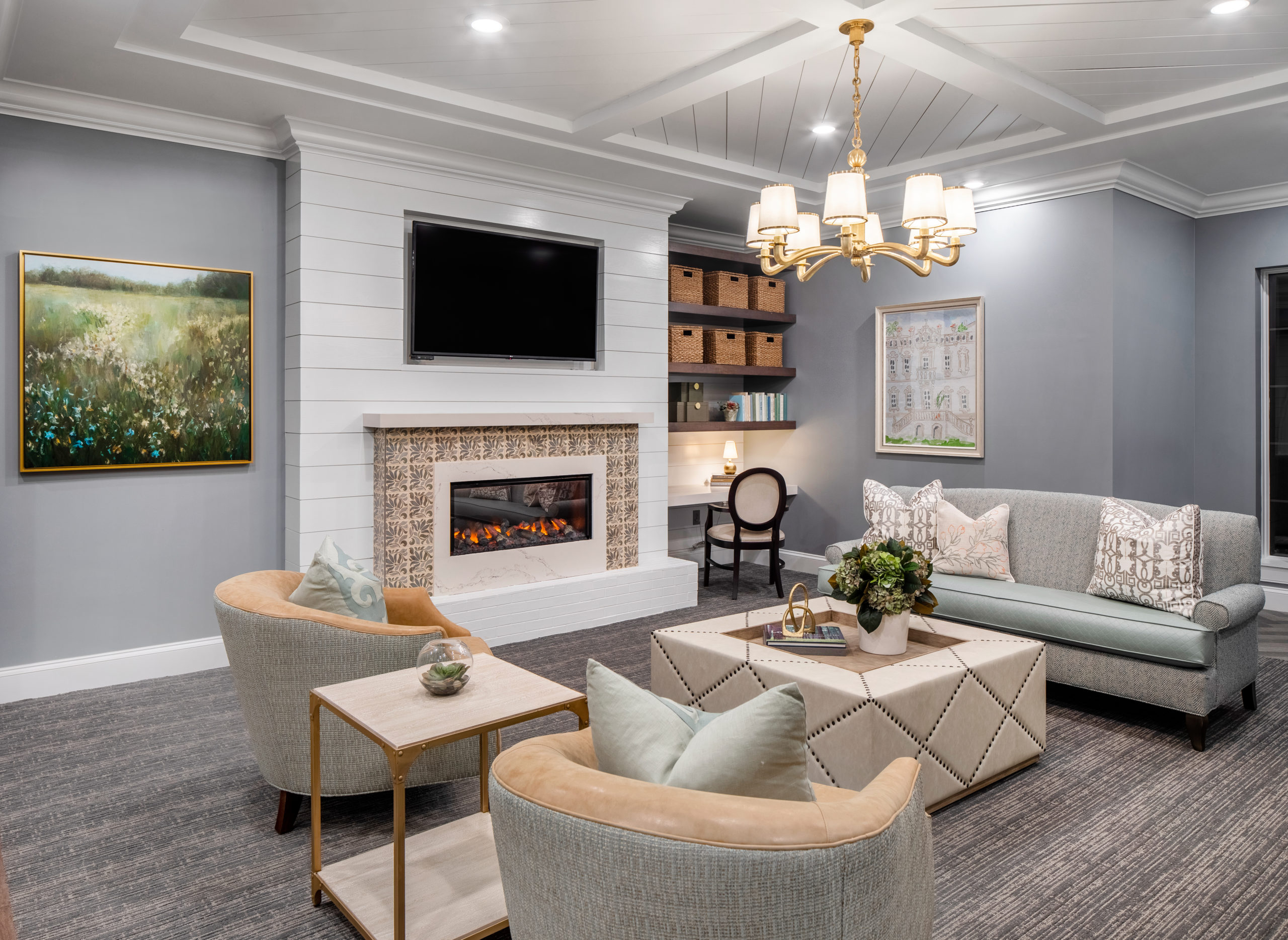 Longleaf common space with TV mounted above fireplace, couches and chairs with ottoman in front