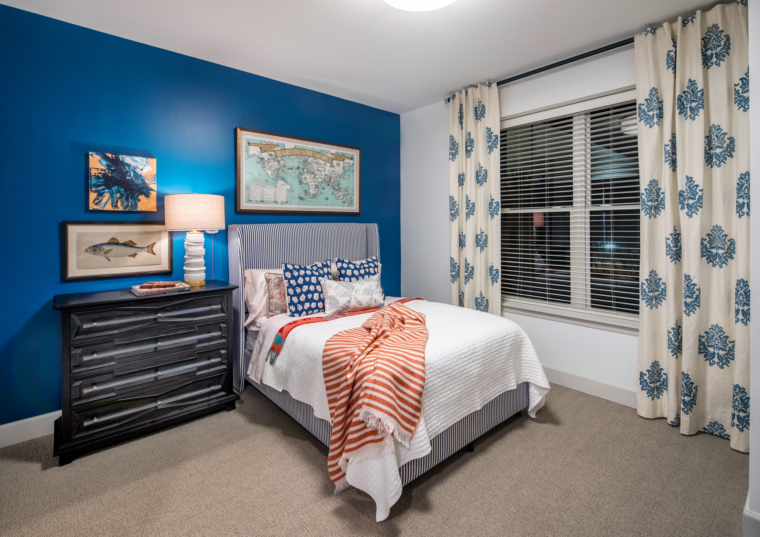 White bed with colorful throw and pillow, black nightstand with lamp and artwork above window and curtains at right in Longleaf memory care model apartment