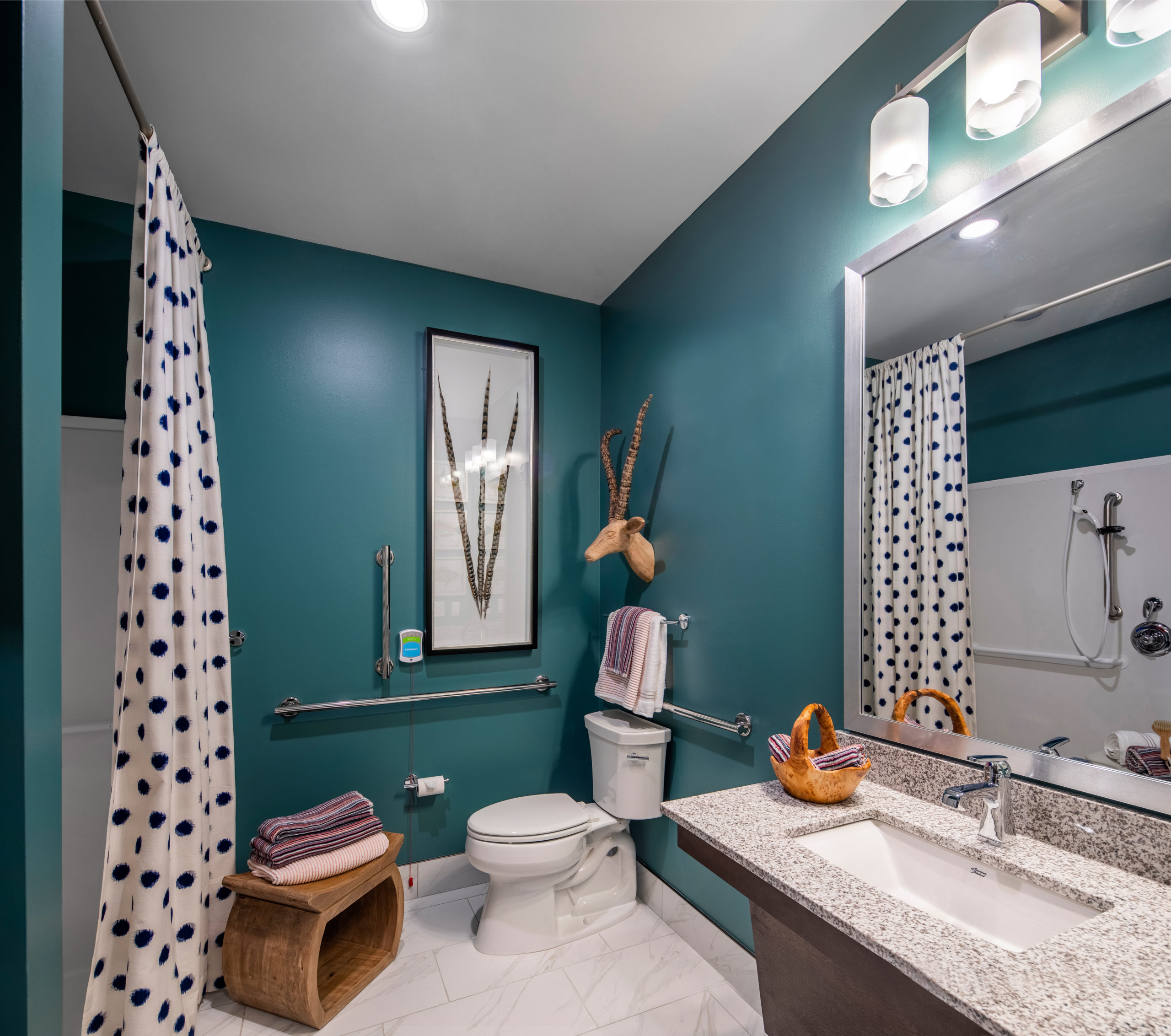 Teal bathroom with white polka dot curtains, granite vanity with sink in Longleaf memory care model apartment