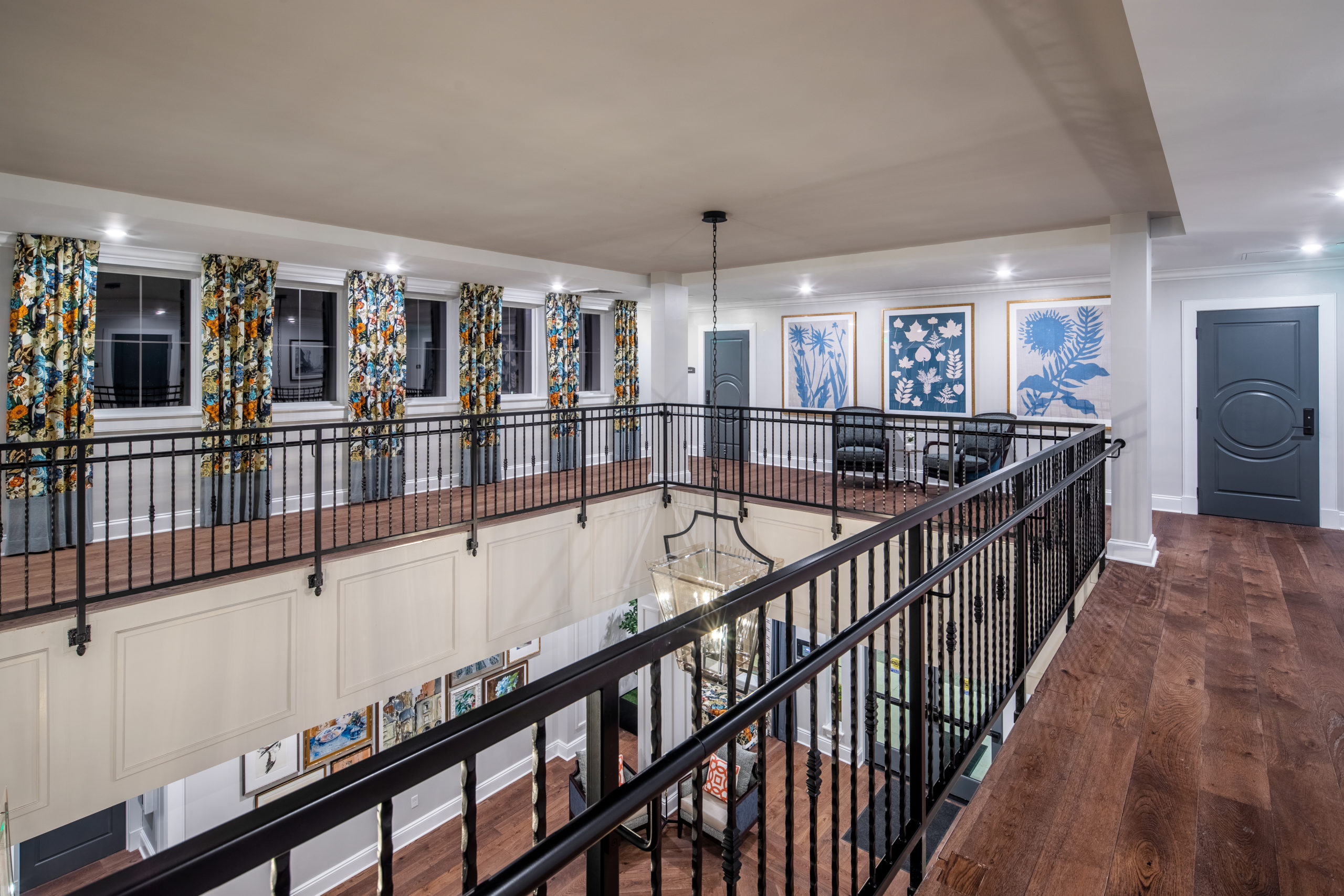 Longleaf second floor atrium with black railing, looking at windows with floral curtains to left, blue doors and paintings to right and first floor foyer below