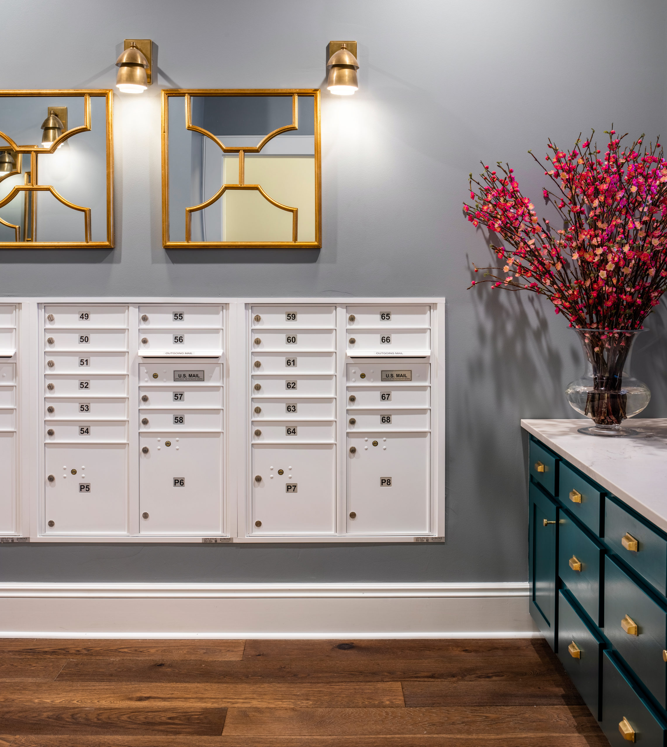 White maildboxes built into grey wall with gold mirrors and light fixtures above mailroom at Longleaf