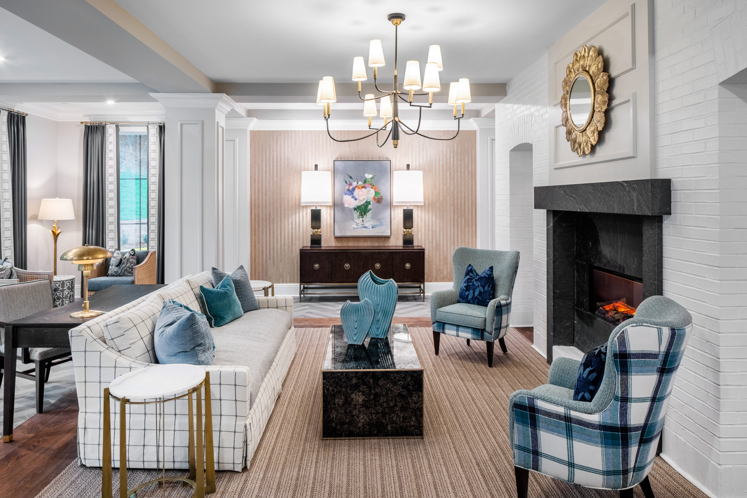 White plaid sofa, black ottoman, blue plaid chairs in front of fireplace in Longleaf common area