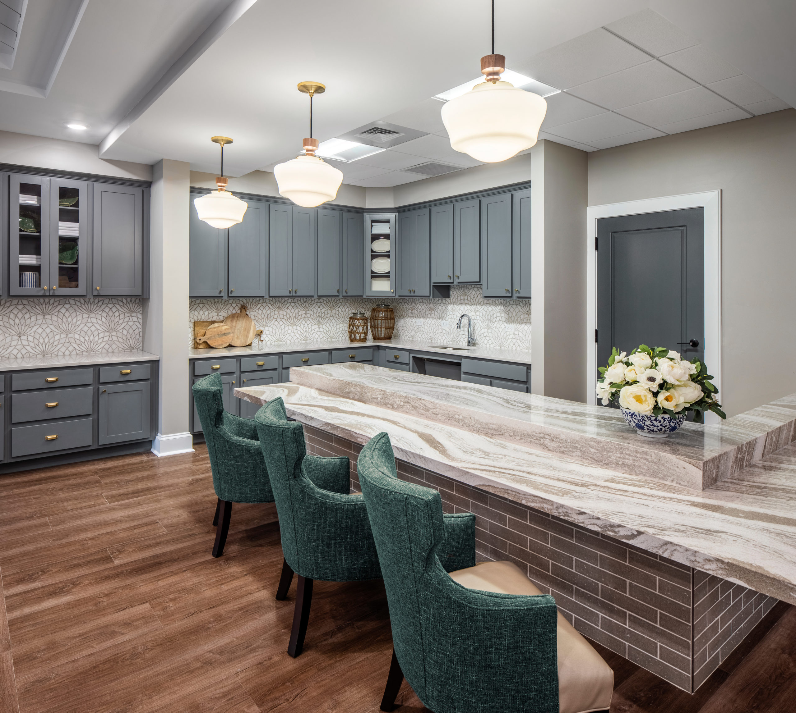 Longleaf memory care dining room bar with three green chairs and grey cabinets at back, three white light fixtures hanging
