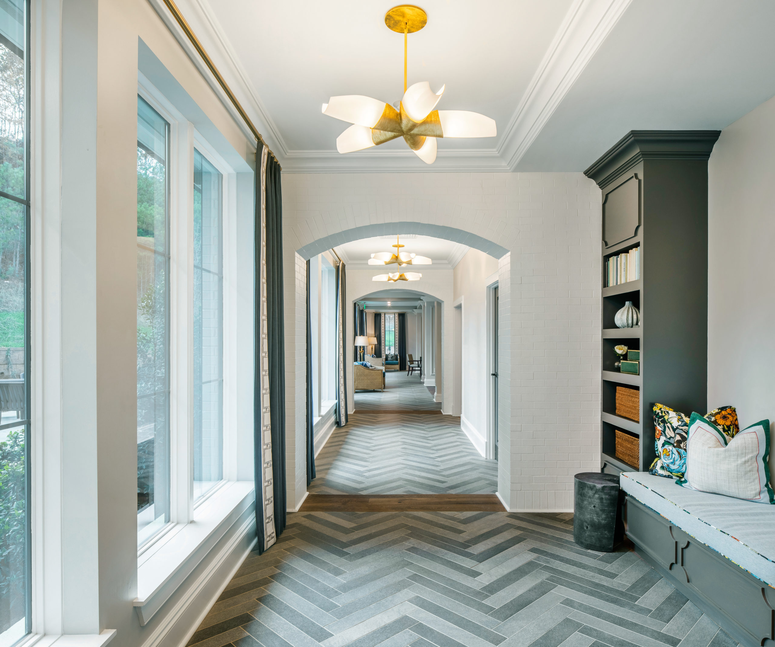Longleaf common space with arched hallway, windows at left, gray shelves, bench seating, white walls and grey chevron pattern on flooring